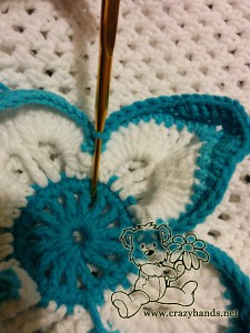 how to crochet a flower for a hat - step #11 (connecting the edge of flower leaf with middle part)