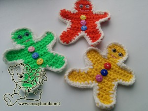 three crochet gingerbread men of different colors: blue, yellow and red