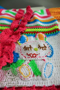 decorate the pocket of the rainbow cardigan with two crochet strawberries