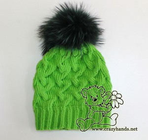 green cable knit hat with dark green raccoon fur pom pom