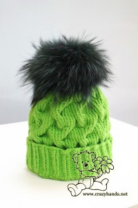 green cable knit hat with dark green raccoon fur pom pom - side view