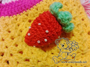 crochet strawberry sewed to the pocket of rainbow cardigan