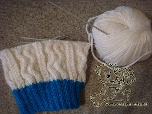 half knitted winter hat, skein of white yarn and needles