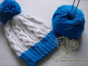 Winter knitted hat with a yarn skein and two needles