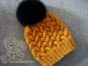 knitted hat with cables and attached black fur pom pom