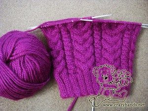 three quarters of the knitted hat length and a skein of wine-coloured yarn