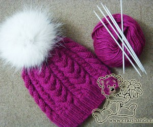 Knitted hat with cables & fur pom pom