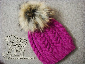 Finished winter knitted hat of wine color with raccoon fur pom