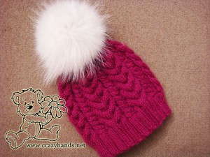 Finished winter knitted hat of wine color with white raccoon fur pom