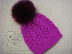 Finished winter knitted hat of wine color with dark red arctic fox fur pom