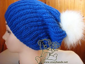 knit slouchy hat with white fur pom pom on the mannequin