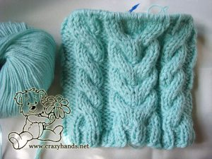 completed body of the knitted hat with earflaps for newborns