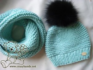 Knitted baby hat with black fur pom pom on the top and matching-style infinity scarf