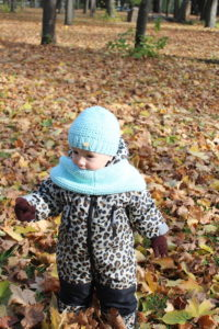 little boy is posing in the ocean blue infinity knit scarf