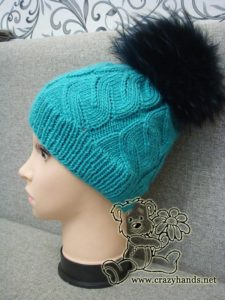 azure cable hat with black raccoon fur pom pom