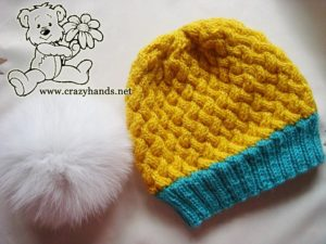 finished simple knit hat with white fur pom pom