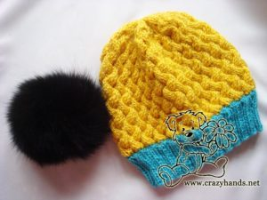 finished simple knit hat with black fur pom pom