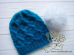 Cable knit hat with white fur pom pom