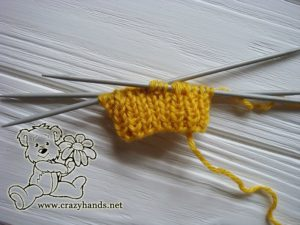 Knitting the ribbing of the mittens for a newborn baby on double pointed needles
