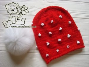 Santa-Style Knit Hat and Fur Pom Pom Beside Each Other